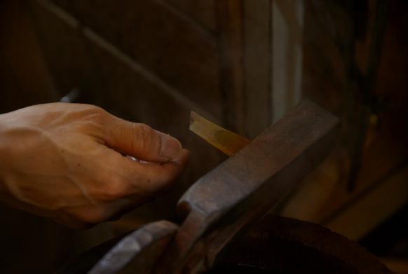 熱した鉄の工具に切り分けられた鼈甲を挟む