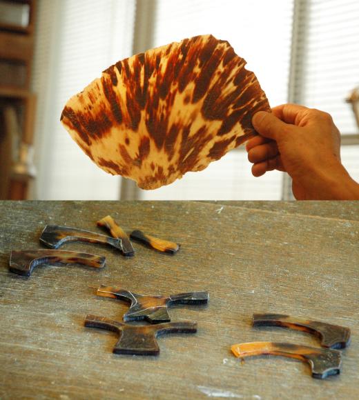 (上)こういう明るい甲羅は珍しい。甲羅の生地取りの仕方で製品の色が大きく変わる為、見極めは慎重に行う。(下)眼鏡の前枠は、2~3枚甲羅から部分ごとに分けて作り、最後に一つの眼鏡につなぎ合わせる。